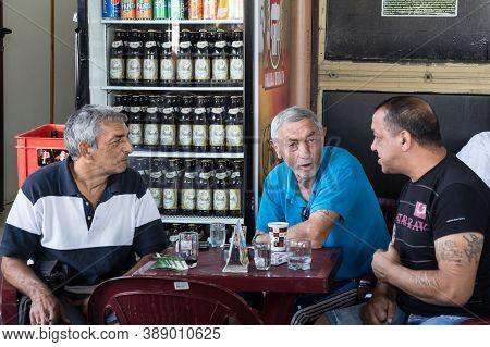 Nis, Serbia - September 3, 2016: Three Senior Men, Serbs, Drinking And Having Fun At A Table Of A Te