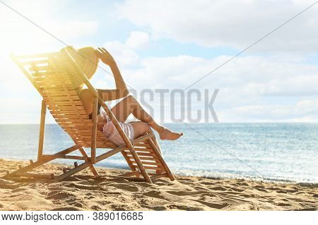 Woman Relaxing On Deck Chair At Sandy Beach. Summer Vacation