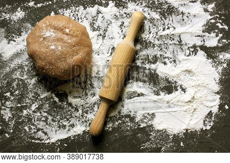 Dough, Rolling Pin And Flour On A Black Background. Ginger Cookie Dough On A Floured Black Surface.