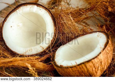 Two Halves Of Coconut On Coconut Fiber Background
