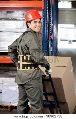 Portrait of young warehouse worker pushing handtruck with cardboard boxes poster