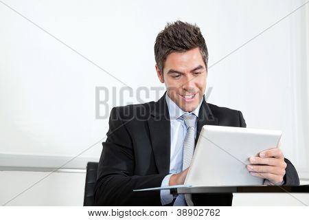 Handsome young businessman using digital tablet at desk in office
