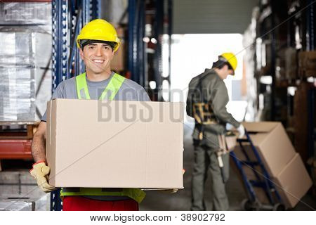 Portrait of happy mid adult foreman with cardboard box and coworker pushing handtruck at warehouse poster