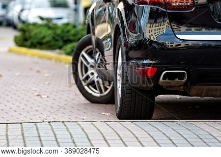Close-up View From Behind Of A Black, Shiny Suv Car Parked On The Pavement In A Parking Lot Near The