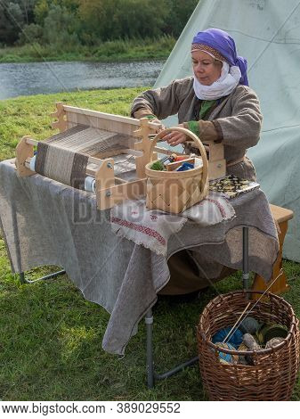 Tver / Russia - September 29 2020: A Woman In A Gray Canvas Dress Works On An Antique Wooden Loom. R