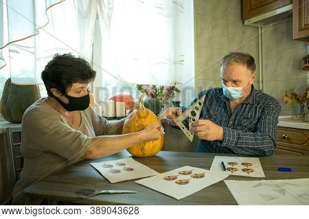 How To Make Jack O'lantern At Home? A Middle Aged Man And Woman Are Doing Jack O'lantern In The Kitc