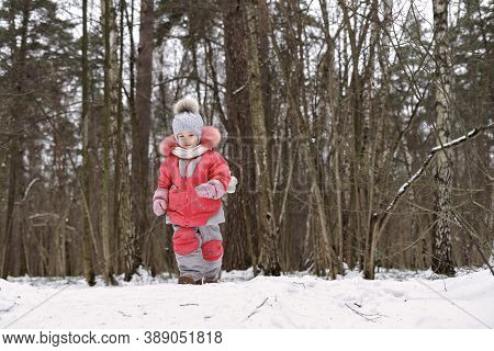 Adorable Little Girl Playing In Winter Park For Christmas Mood. Children Play Outdoors
