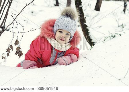 Adorable Little Girl Playing In Winter Park . Fun In The Fresh Air For A Christmas Mood