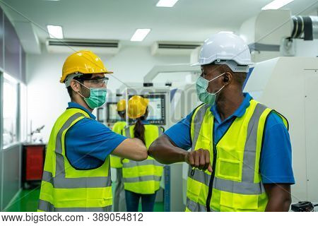Engineer Greeting Bumping Elbows In Factory,new Novel Greeting To Avoid The Spread Of Coronavirus.