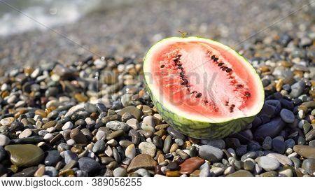 Ripe Watermelon Lies On The Seashore. The Cut Watermelon Lies On The Seashore. Watermelon In The Sea