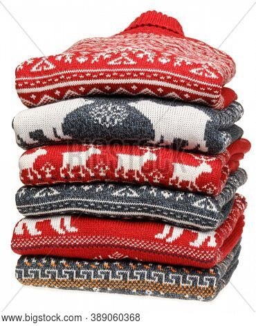 Stack of folded knitted Christmas turtleneck sweaters or pullovers with nordic ornament isolated on white background