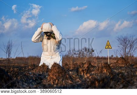 Scientist In Gas Mask And Protective Suit Staring At Burnt Field And Grabbing Head With Hands In Des