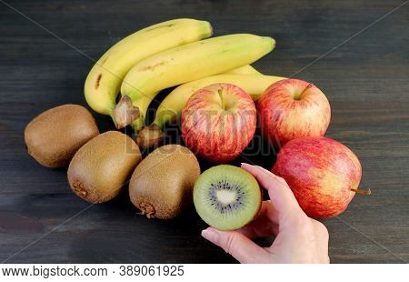 Assorted Fresh Ripe Fruits On Black Wooden Background With Hand Holding A Cut Kiwifruit For The Conc