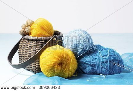 Skeins Of Blue, Blue, Yellow Yarn Lie On A Light-blue Background, Next To It There Is A Wicker Baske