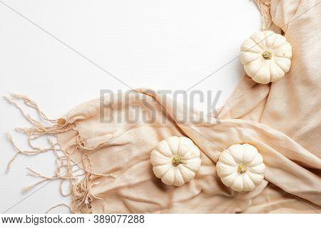 Elegant Autumn Composition. Small White Pumpkins And Beige Scarf On White Table. Autumn Fashion Conc