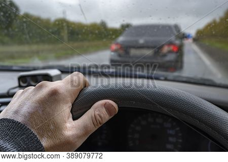 The Driver Hand On The Steering Wheel Of The Car Against The Background Of The Car In Front, Which I