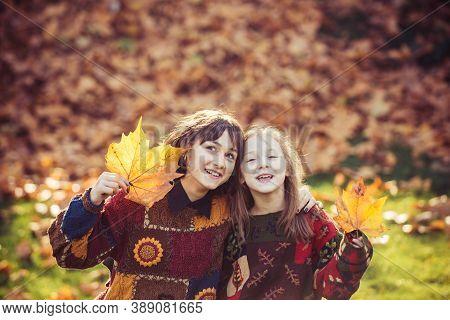 Happy Smiling Girls In Autumn Park. Beautiful Girl With Sister In Golden Park. Smiling Girl With Sis