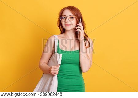 Portrait Of Beautiful European Woman Talking On Mobile Phone Against Yellow Background, Wearing Casu