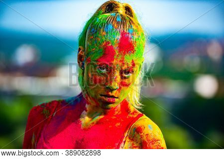 Color Face With Colorful Holi Splash. Close-up Portrait Of A Young Woman With Colorful Holi Powder.