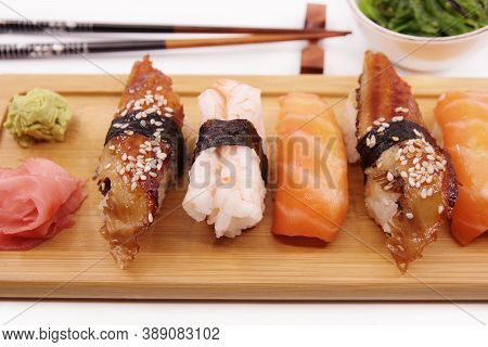 Japanese Sushi Food. Sushi Set On Wooden Tray Served With Ginger, Soy Sauce And Seaweed Salad. Sushi