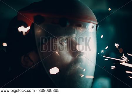 Man In Transparent Protective Mask With Flying Sparks In Darkness.