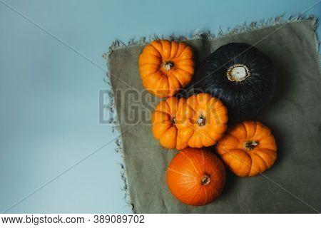 Top View Decorative Pumpkins On Green Napkin. Autumn Harvest Composition On Trendy Earth Tones Color
