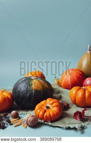 Orange And Green Decorative Pumpkins, Apples, Nuts And Fallen Leaves In Autumn Harvest Composition O