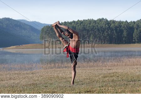 Indian Man Doing Yoga Exercises Outdoors In Kerala State, South India