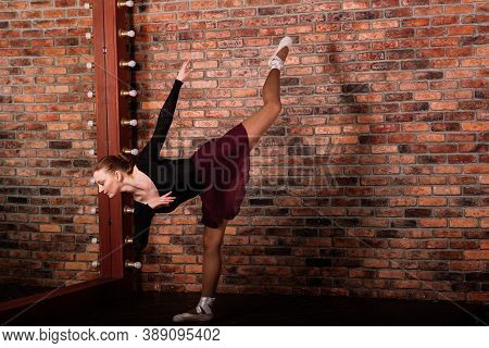 Beautiful Female Classical Ballet Dancer On Pointe Shoes Wearing Leotard And Skirt In Studio