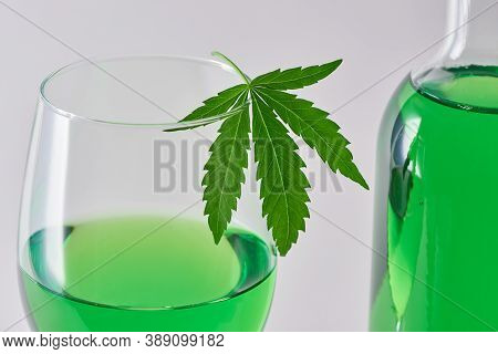 Close-up On A Glass And A Bottle Of Green Weed Wine On Light Background