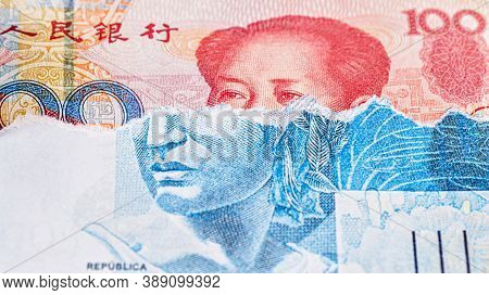 Banknote Of 100 Reais From Brazil, Torn, Revealing A Hundred Yuan Note Underneath. Concept Of Crisis