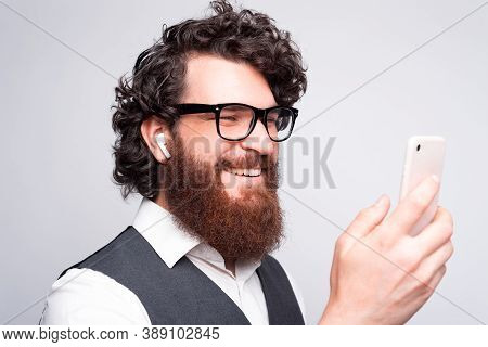 Close Up Portrait Of Young Bearded Hipster Man Using Smartphone And Earpods Over White Wall