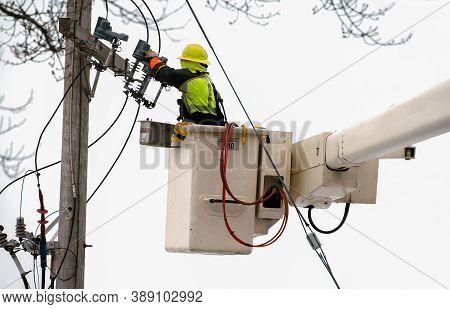 Man Working On Power Transformer In Lift Boom Bucket
