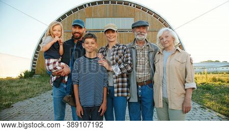 Portrait Happy Caucasian Family Of Three Generations Standing Outdoor At Farm Shed And Smiling To Ca