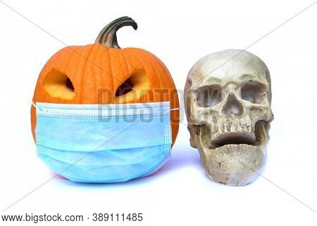 Halloween Pumpkin. Halloween Jack O Lantern with a Paper Face Mask. Isolated on white. Room for text. Coronavirus is dangerous, wear your mask! Pumpkin with a Human Skull.
