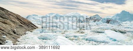 Global warming - Greenland Iceberg landscape of Ilulissat icefjord with giant icebergs. Icebergs from melting glacier. Arctic nature heavily affected by climate change.