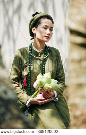 Portrait Of Pensive Young Woman With Lotus Flowers Sitting Outdoors In Traditional Ao Dai Dress