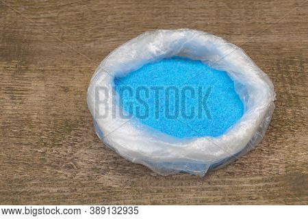 Copper Sulphate Crystals In A Bag, Wooden Background
