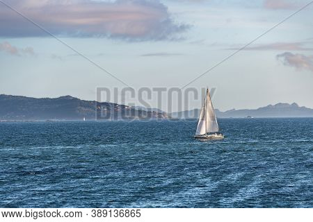 A Lonely Boat Sails Away From The Ria De Pontevedra In Galicia At Dusk, With The Cies Islands In The