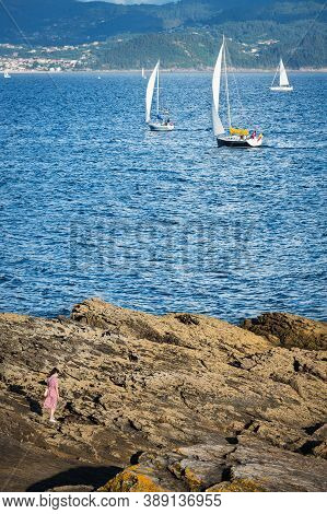 Portonovo, Spain - August 15, 2020: A Young Woman Walks On The Rocks With A Handful Of Small Boats D