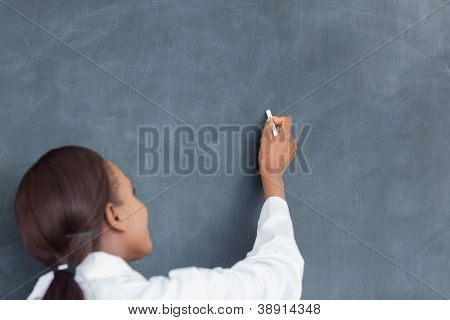 Rear view of a teacher writing on a blackboard in a classroom