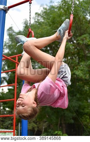Caucasian Teenager Girl On Gym Outdoor Playground. Children's Sports For Health. A Girl Of 10-14 Yea
