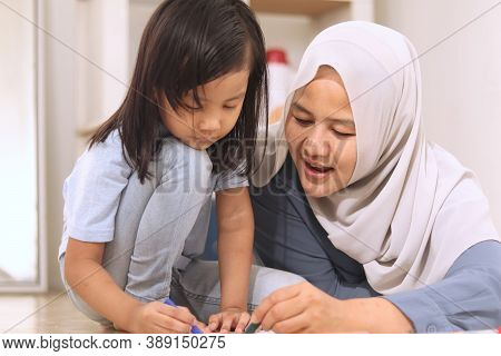 Asian Muslim Mother Drawing With Her Daughter, Single Mom Teaching Baby Girl, Learning On The Floor,