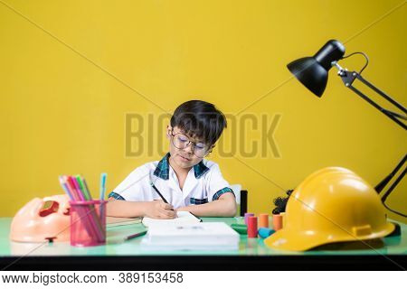 Boy Doing Homework, On The Table There Are Learning Materials.