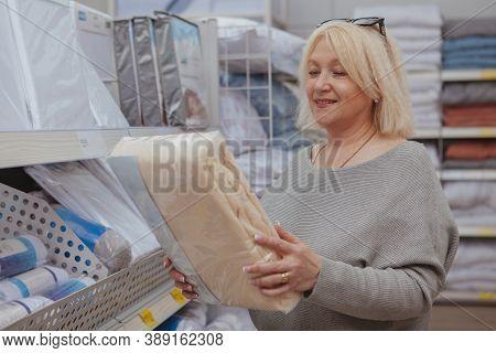 Mature Cheerful Woman Smiling, Choosing New Bedsheets At Furnishings Store. Happy Female Customer Bu