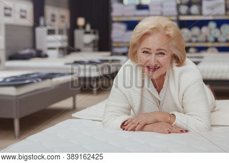 Lovely Senior Woman Laughing To The Camera Lying On Orthopedic Mattress At Furniture Store, Copy Spa