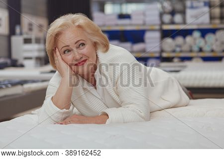 Lovely Happy Elderly Woman Looking Away Dreamily, Lying On Orthopedic Comfortable Mattress At Furnit
