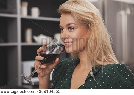 Stunning Young Blonde Woman Smiling Joyfully, Looking Away Drinking Wine At Home. Beautiful Happy Fe
