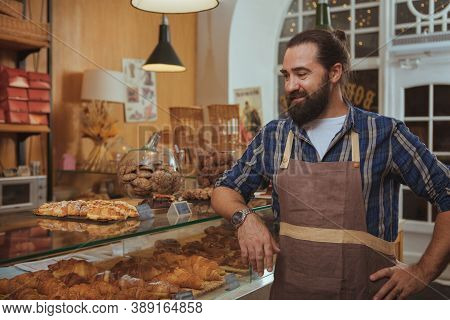 Proud Mature Male Baker Smiling, Looking At His Freshly Baked Pastry On The Display, Copy Space. Bea