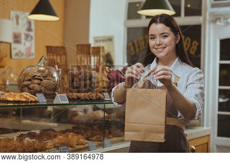 Beautiful Cheerful Female Baker Smiling, Holding Out Paper Shopping Bag To The Camera, Working At He